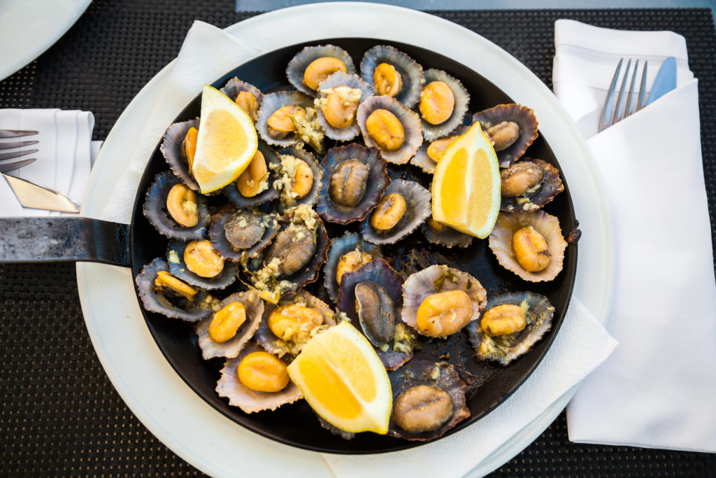 delicious maderian seafood - grilled limpets served with lemon